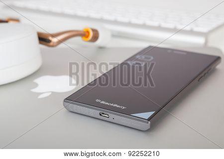 BlackBerry Leap smartphone back, Apple MacBook Pro Retina and Parrot Zik ear-laps