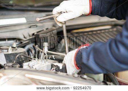 Closeup of an auto mechanic working on a car engine