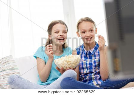 people, children, television, friends and friendship concept - two happy little girls watching comedy movie on tv and eating popcorn at home poster