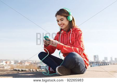 technology, lifestyle and people concept - smiling young woman or teenage girl with smartphone and headphones listening to music outdoors