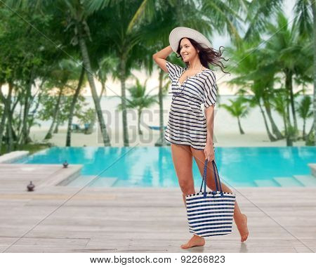 people, fashion, summer and beach concept - happy young woman in summer clothes and sun hat with bag over swimming pool at beach resort