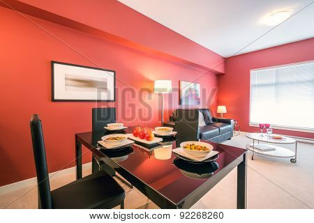 Modern red kitchen with a living room in a luxury apartment. Interior design.