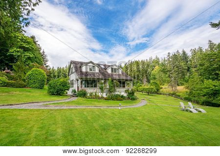 Rustic country house with a large lawn and beautiful landscaping.