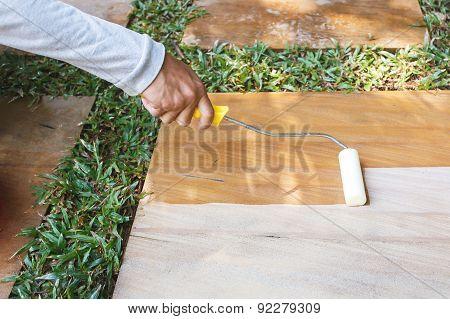 Worker Using Roller Apply Sealer On Sandstone