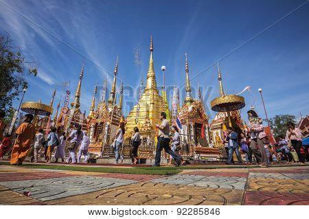Buddhist people praying and walking around a golden pagoda.