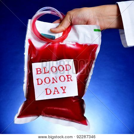 closeup of the hand of a doctor holding a blood bag with a sticker with the text blood donor day
