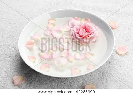 Bowl of aroma spa water with rose petals on towel, closeup