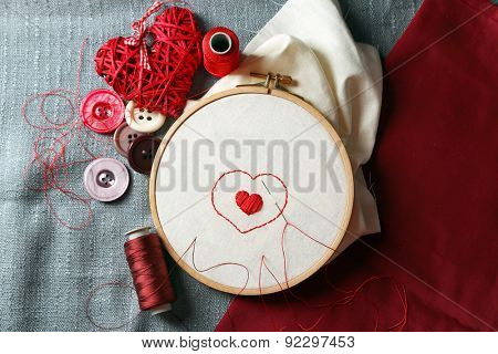 The embroidery hoop with canvas and red sewing threads on table close up poster