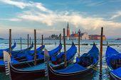 Gondolas moored by Saint Mark square with San Giorgio di Maggiore church in the background at twilight in Venice lagoon, Italia poster