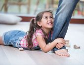 Low section of father dragging girl on hardwood floor poster