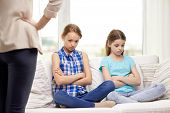 people, children, misbehavior, friends and friendship concept - upset feeling guilty or displeased little girls sitting on sofa and angry mother at home poster
