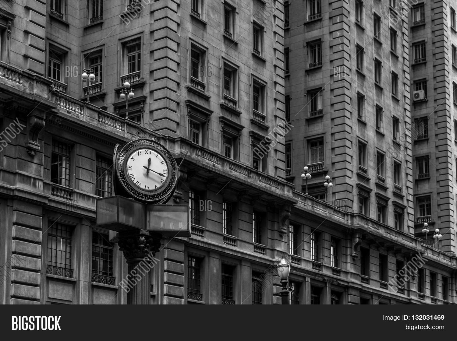 Black and white iconic old style street clock in front of buildings with windows with old