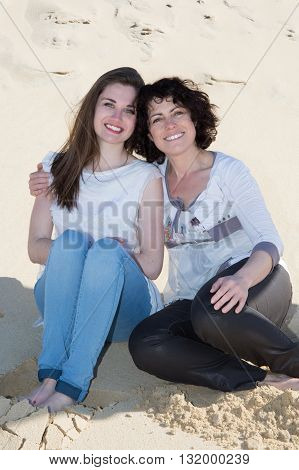 Mother And Adult Daughter Posing On The Sand On Holidays
