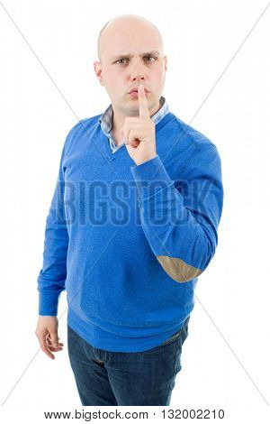 portrait of a young bald man making a shushing gesture with his finger, isolated on a white studio background.