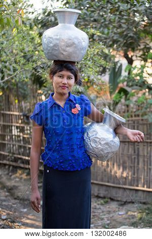 MRAUK-U MYANMAR - JANUARY 27 2016: Unidentified Burmese girl with big jugs with water. The local people are hospitable and friendly to tourists