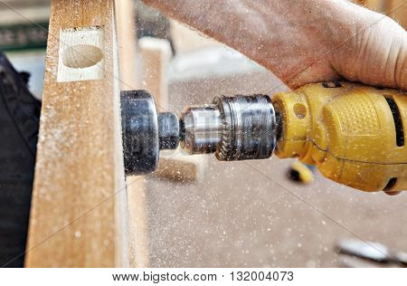Door installation drilling a big hole through the door using yellow electric drill with hole saw drill bits for lock doorknob close-up.