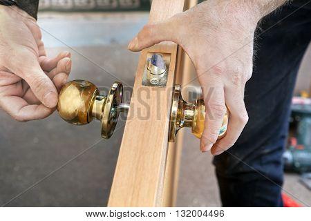 Door installation worker Installs door knob woodworker hands close-up.