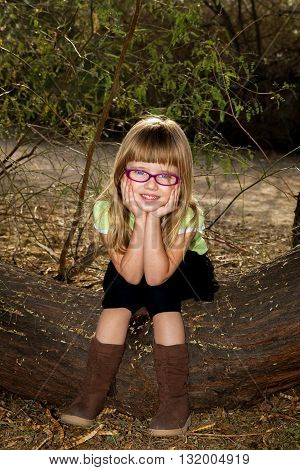 A cute girl sits on a log with her chin in her hands. She is wearing pink glasses and boots with knee length leggins.