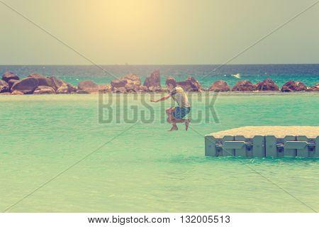 A boy jumps into the sea in Aruba