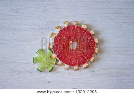 Gear drive made of citrus slices on wooden background