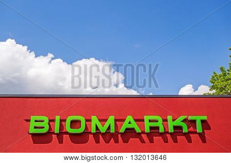 "Heidenheim, Germany - May 26, 2016: Organic food market / bio market, red facade labeled with ""BIOMARKT"", german language, blue sky with clouds poster"