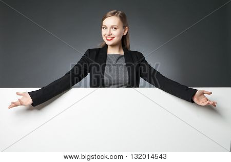 Woman presenting blank space with wide arms