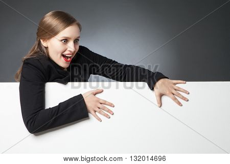 Wide-eyed woman with red lips looking down in surprise