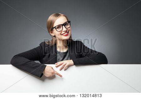 Portrait of beautiful young woman in glasses with red lips pointing with index finger at white space