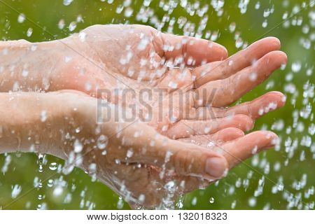 hands of woman catching raindrops on blurred background