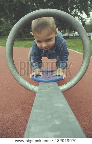 Happy child boy playing seesawing in green grass playground in park