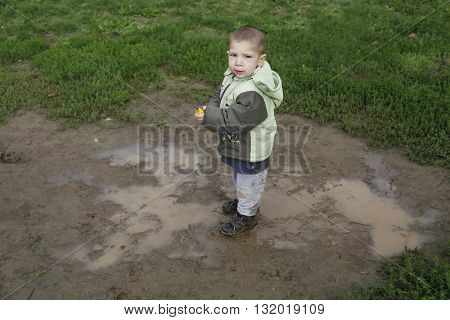 Two years child walk and playing in mud puddle in park