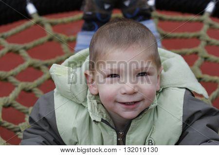 Little Child In Autumn Jackets Swinging In A Swing