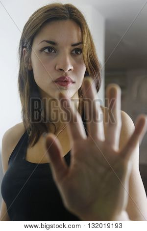 Girl holding hand on door glass showing the fear