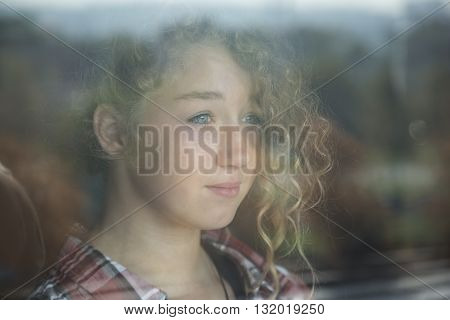 Portrait of Beautiful Redhead Girl Behind Glass with reflection at home
