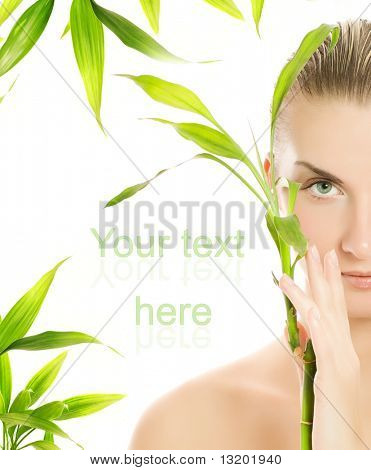 Beautiful young woman with a bamboo plant