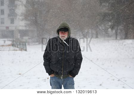 Older man with greybeard in senior fifty on snowstorm outside in the park