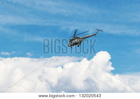 Large military helicopter flies into the side of a blue sky with clouds