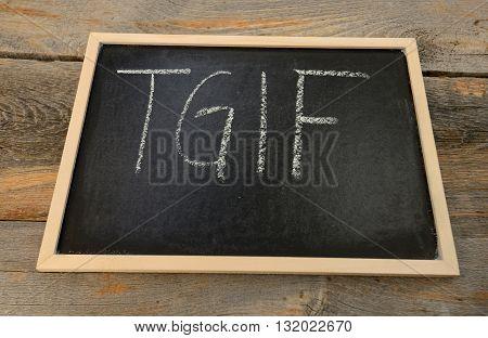 Thank god it's friday - TGIF - written in chalk on a chalkboard on a rustic background