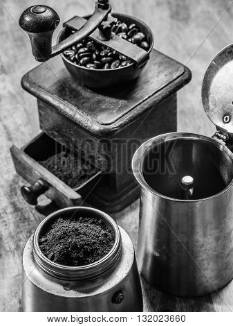 Photo of an Italian Moka Express stovetop coffee maker and a coffee grinder done in black and white.