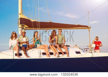 Smiling people on small yacht. Guys and girls holding drinks. Captain is watching the horizon. Perfect weather for sailing.