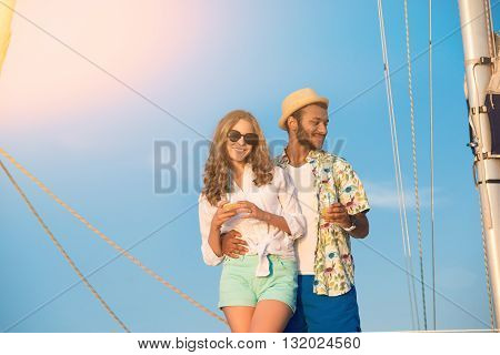 Man and woman smiling. Couple with drinks on yacht. Dear friend of mine. Charge of positive emotions.
