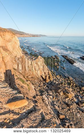 A rocky cliff view of the Pacific ocean at low tide in Carpinteria California.