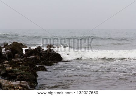 Waves Over The Rocks On The Beach