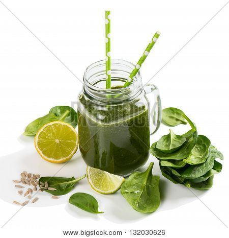 Vegetable smoothie of spinach with lemon and seeds of sunflower in a mason jar isolated on white background.