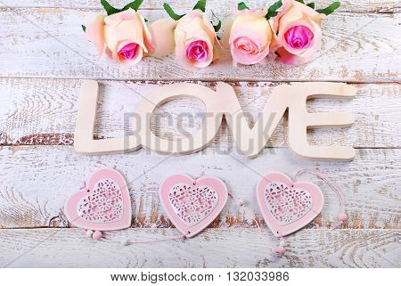 romantic love background with word lovehearts and roses on white wooden planks
