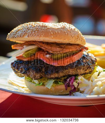 Tasty beef hamburger with a 300 gram piece of beef fried bacon tomato pickles and onion. Served in a sesame bread roll