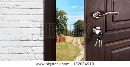 Entrance door half opened to nature background. Door handle, door lock. Exit outdoors. Opening door. Entrance to the house. Door at white brick wall, summer countryside and freedom concept.