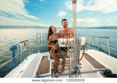 Smiling people at yacht wheel. Guy with girl on yacht. Another day in open sea.