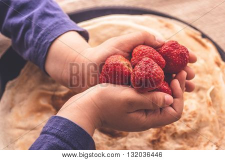 Fresh strawberries in child hands over  plate with fresh french pancakes close up macro matte abstract idea of happiness and family