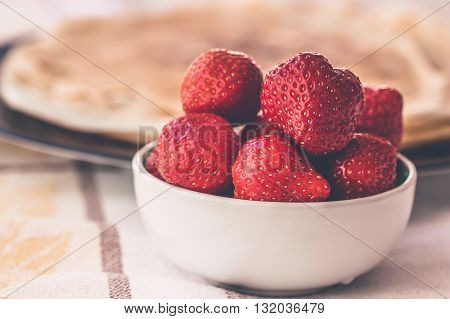 Fresh strawberries in white bowl with french pancakes crepas in the background on Saturday morning breakfast, selective focus, healthy nutrition. Abstract family happiness concept
